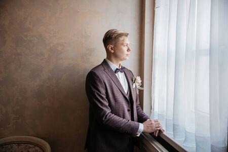 close up. brooding groom standing near the window.