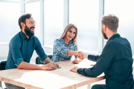junge Geschäftsfrau, die einem neuen Mitarbeiter des Unternehmens die Hand schüttelt Standard-Bild