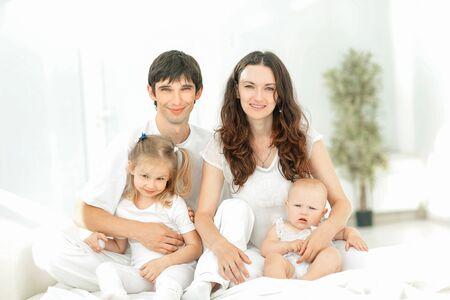Famiglia felice che si gode la mattina a letto Archivio Fotografico