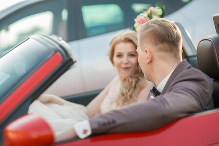 happy bride and groom sitting in a luxury car.