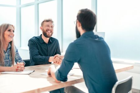 Manager shaking hands with the applicant during the interview