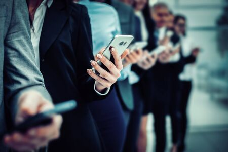 group of diverse employees with smartphones standing in a row