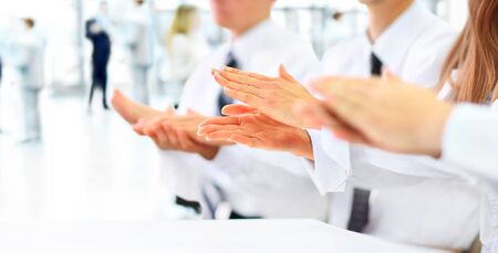 Close-up of business people clapping hands.
