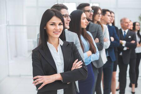 mujer de negocios joven de pie delante de sus colegas. el concepto de trabajo en equipo Foto de archivo