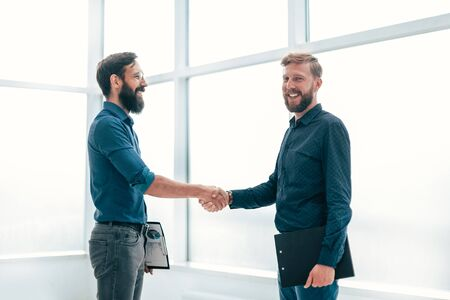 financial pratners shaking hands while standing in the office.