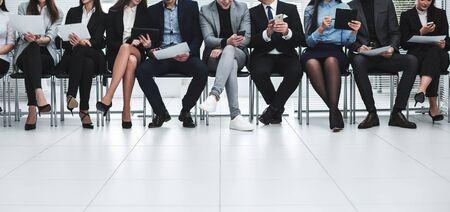 un groupe d'hommes d'affaires utilise leurs gadgets avant de commencer une réunion d'affaires