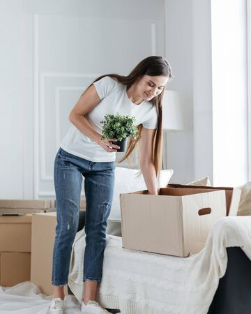 happy young woman takes things out of cardboard boxes