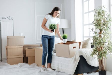 young woman taking personal items out of a cardboard box