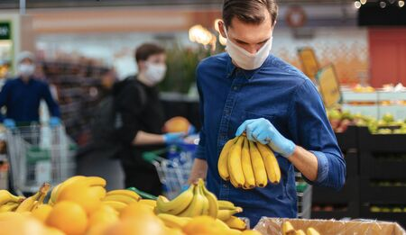 man in protective gloves choosing bananas in a supermarket. Stock Photo