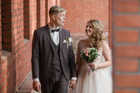 bride and groom standing in an old red brick building . Archivio Fotografico