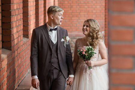 bride and groom standing in an old red brick building . Foto de archivo