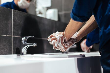 Young man soaping his hands under the tap
