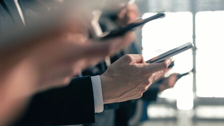 A group of young business people with smartphones