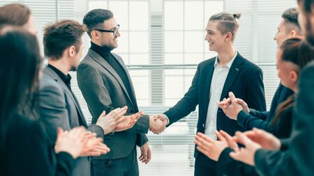 business partners shaking hands to the applause of the business team