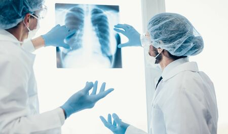 close up. scientists in protective masks looking at an x-ray of the lungs .