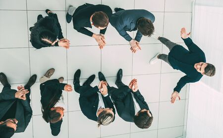 top view. business team applauding their comrade.