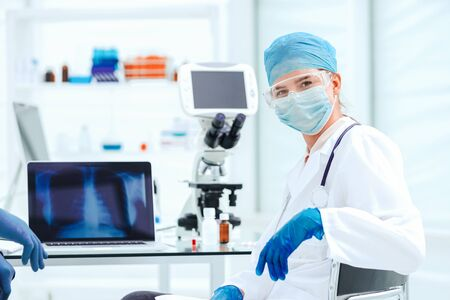 female doctor in a protective mask sitting at a laboratory table.