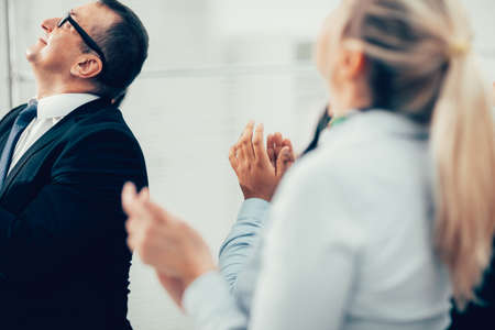 group of business people applauding standing in the office