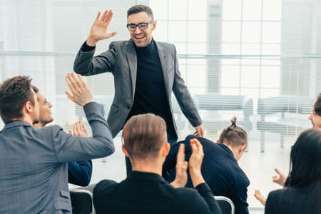 employees giving each other a high five during a work meeting 版權商用圖片