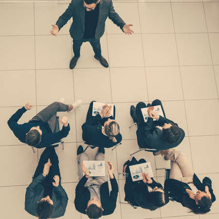top view. group of employees applauding at a work meeting.