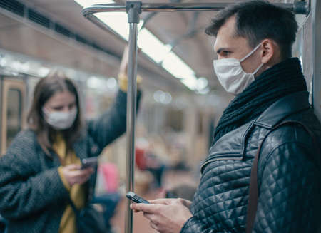 passengers in protective masks standing in the subway car.