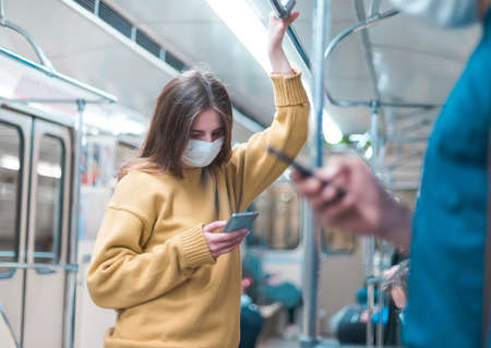 people with smartphones standing in a subway car.
