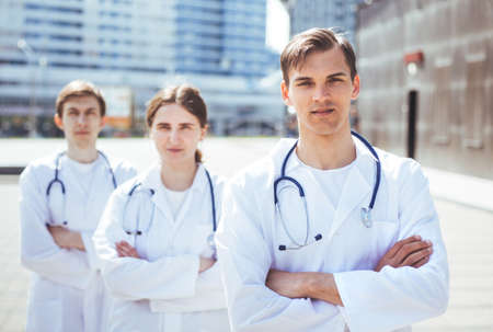 group of medical professionals standing on a city street.