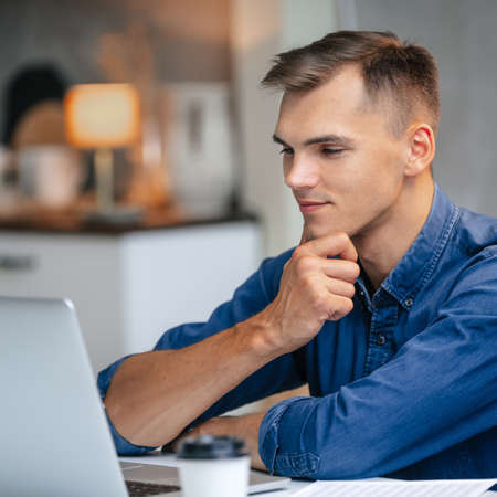 male freelancer works on a laptop in his kitchen.