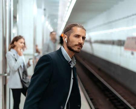 young man waiting for a train at subway station. Banco de Imagens