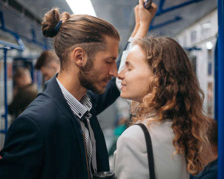 man and woman in love looking at each other on a subway train.