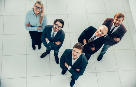 top view. a group of smiling business people looking at the camera.