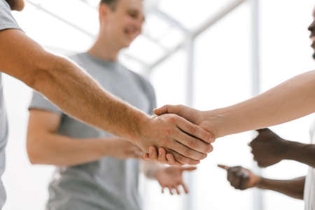close up. two comrades shaking hands, standing in a circle of friends