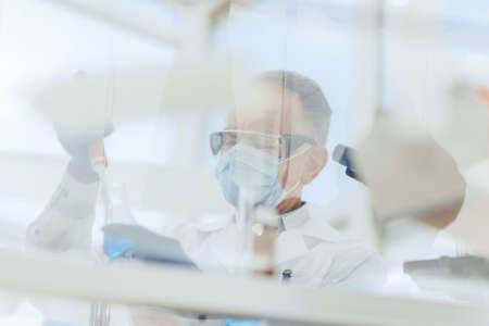scientist sitting using an automatic dispenser for his research.