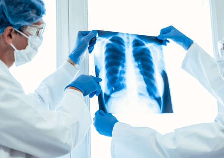 close up. doctors in protective masks looking at an x-ray of the lungs .