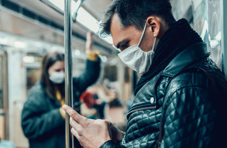 passenger in a protective mask reading a message on his smartphone. Foto de archivo