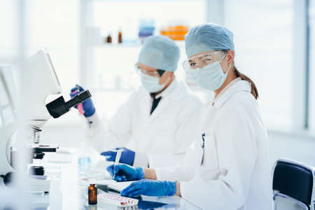 scientists testing the liquid and writing the results in a laboratory journal. Stock fotó