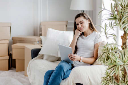 young woman with digital tablet sitting on a comfortable sofa