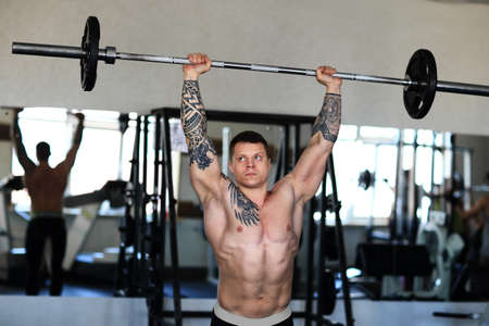 bodybuilder works with a barbell in the gym.