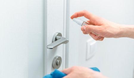 close up. neat man spraying antiseptic spray on the door handle.