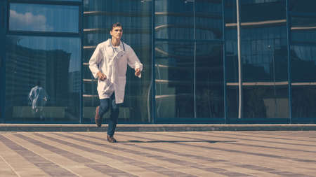 doctor with a stethoscope runs quickly along a city street. Stock fotó