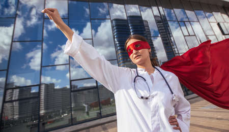 female doctor in a superhero Cape is ready to help .