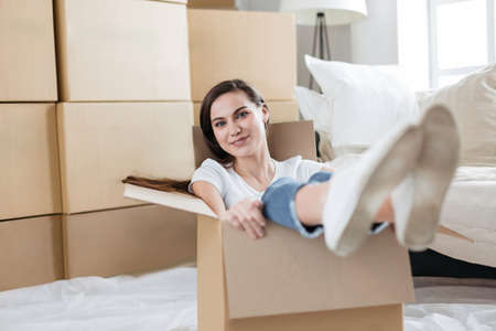 happy young woman sitting in a large cardboard box