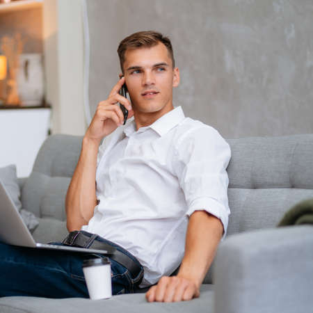 young man is talking on a smartphone, sitting on the sofa. Stock fotó