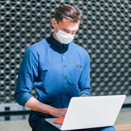 man in a protective mask spraying a bactericidal spray on the surface of a laptop. Stock fotó