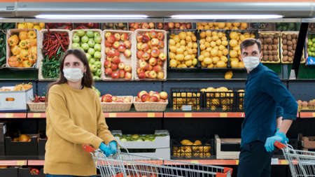 man and a woman with shopping carts in a supermarket during the quarantine period.