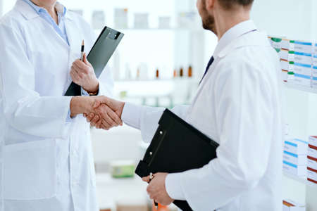 doctor and the pharmacist, shaking hands with each other.