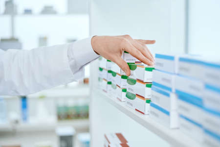 image of a pharmacist taking a box of medicine.