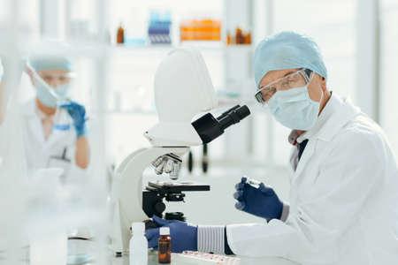 scientist using a microscope in a biochemical laboratory.