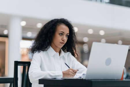 young woman works sitting at a table in a food court .