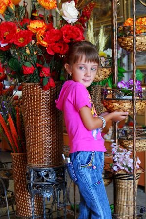 The girl in a pink blouse and jeans is photographed among flowers. Фото со стока